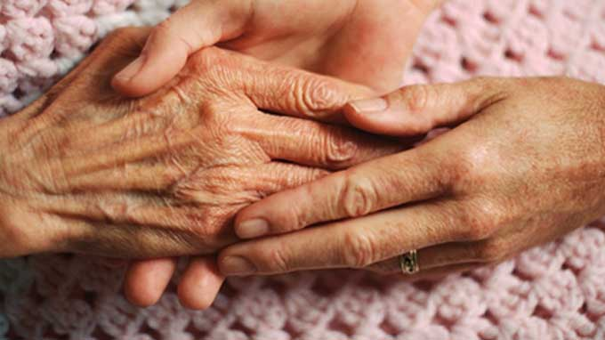 Elderly person's hands holding another person's hands on bedspread. Palliative clients and their families make the decision to stay at home with care for a variety of reasons