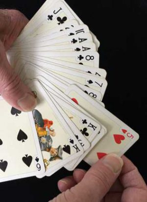 magic trick with 5 of hearts being shown
