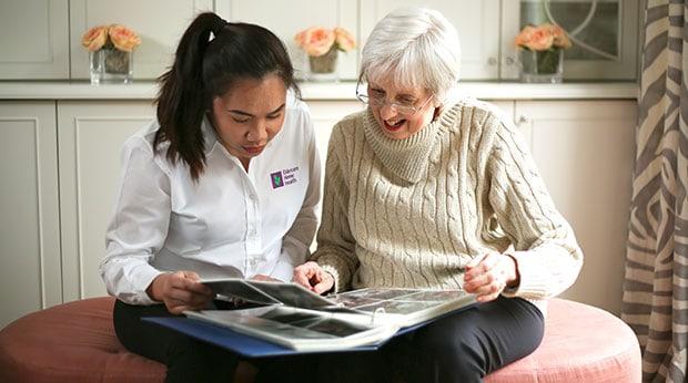 Senior and caregiver looking at photo album