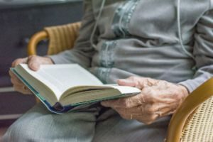 Elder person sitting, reading